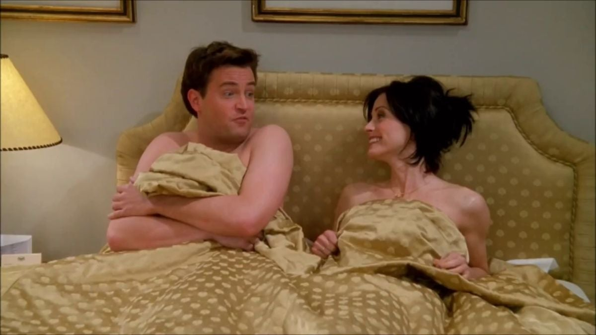 Chandler and Monica are in bed, hiding under the covers