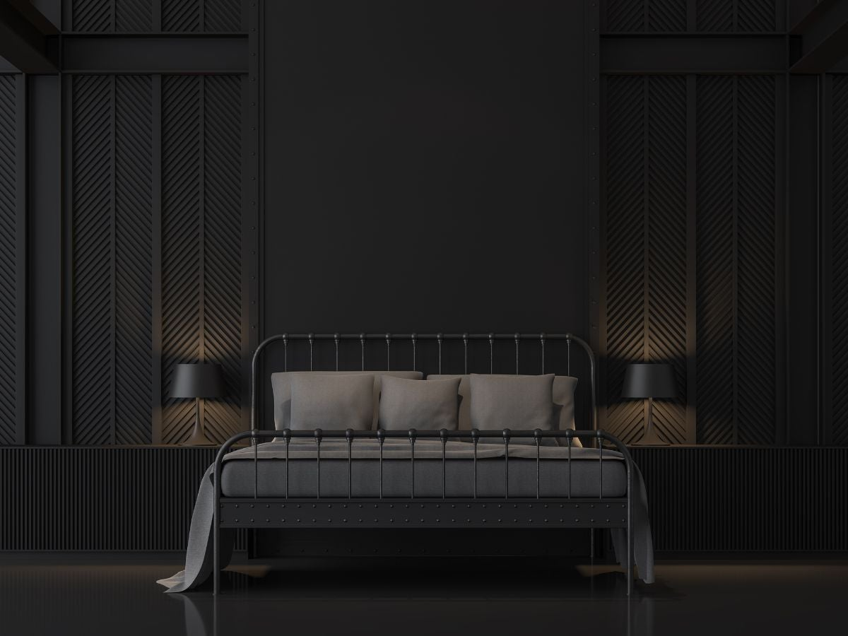 A dark bedroom with a bed in the middle of the room with a wire frame and two identical nightstands with two identical lamps on either side