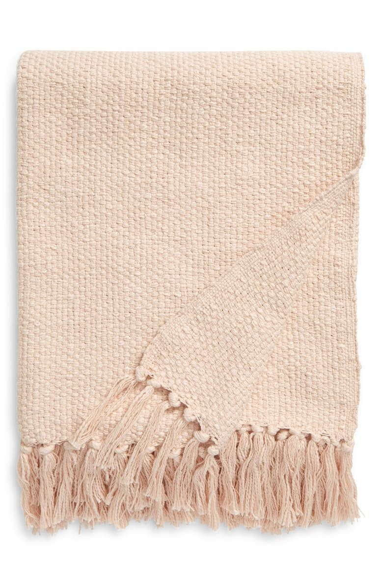 light pink woven blanket with fringe on the ends