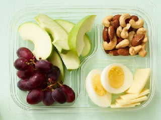 Hard-boiled eggs, cheese, apple slices, grapes, and nuts
