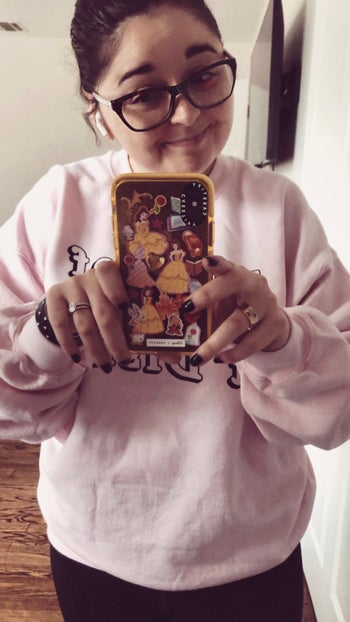 a photo of buzzfeed editor holding the belle phone case