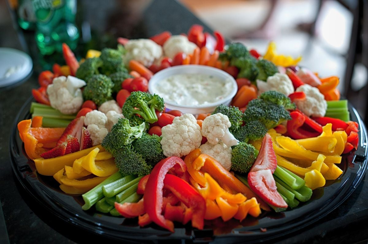 A tray of celery, broccoli, cauliflower, red bell peppers, yellow bell peppers, orange bell peppers, cherry tomatoes, and carrots with a container of ranch in the middle