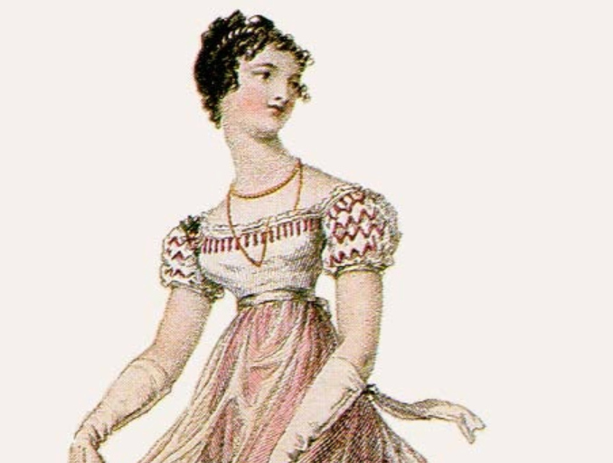 A woman with curly hair wears a long gold necklace and a dress with puffy sleeves. The dress is also slim on the bottom with a ribbon around the waist