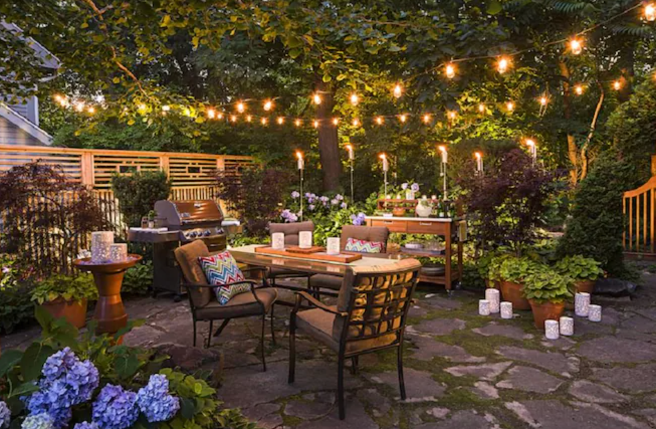 string lights hanging over patio furniture in a backyard