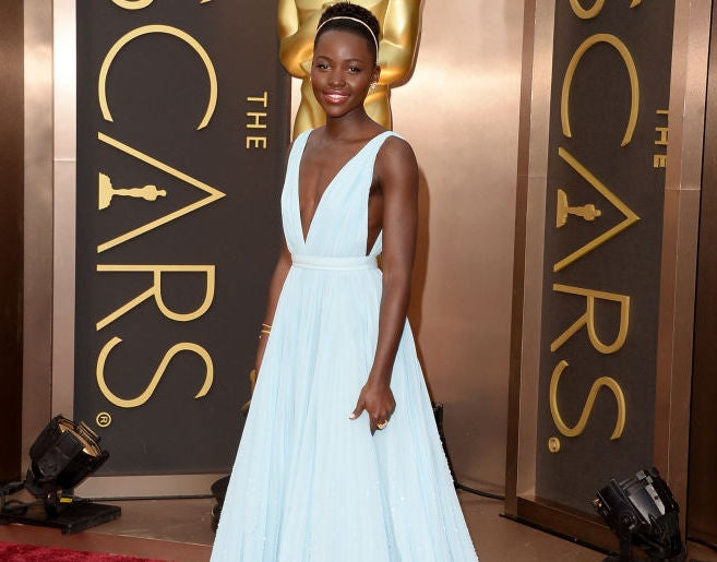 Lupita Nyong'o wearing a long, flowing gown with a plunging neckline