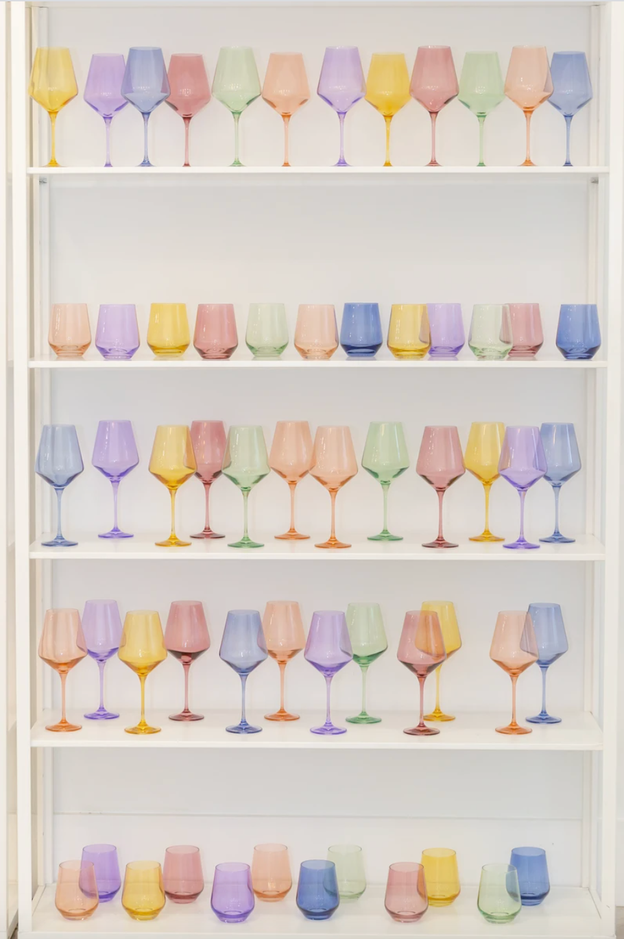 A variety of colored glassware sits inside a white display cabinet