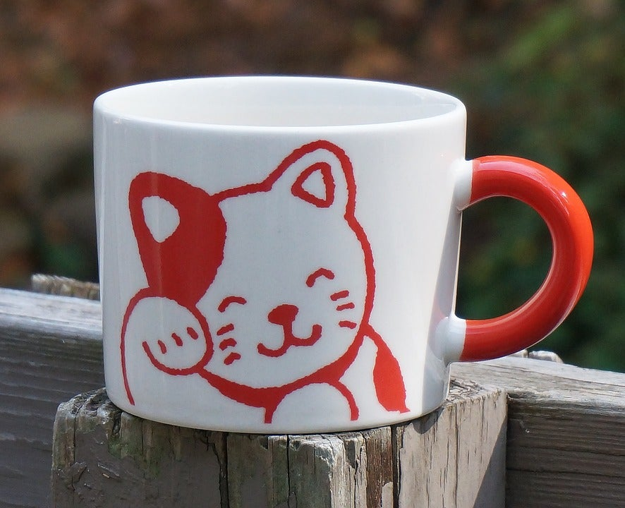 Mug with illustration of a cat washing its face with its paw