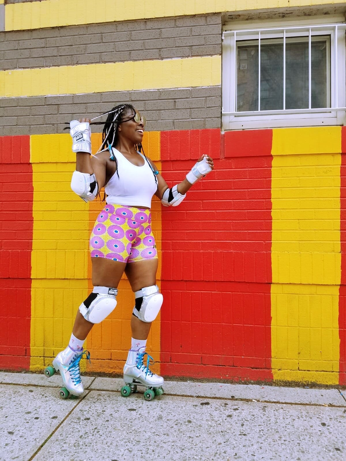 model wears yellow and pink-print bike shorts while wearing roller skates