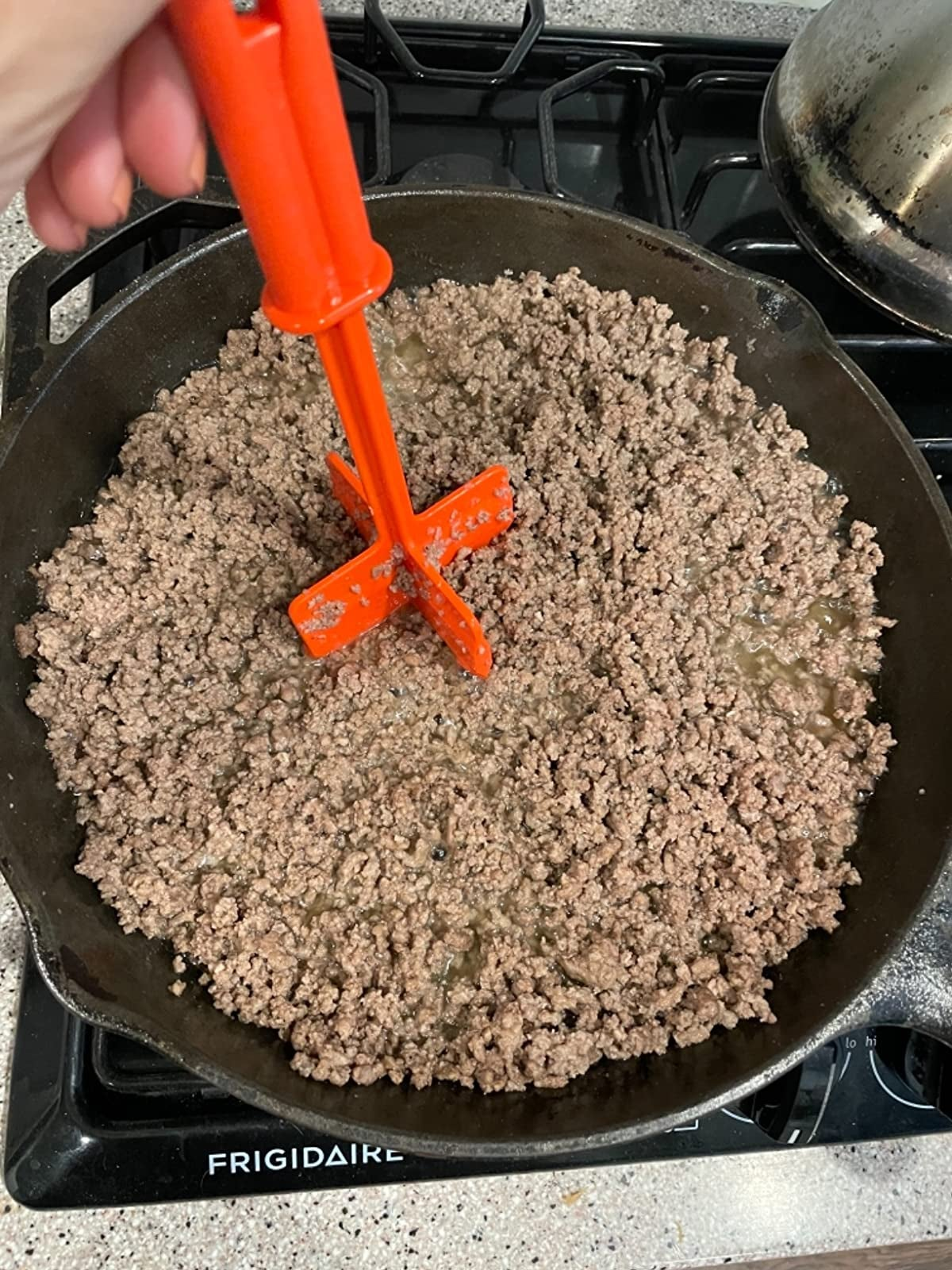 a reviewer chopping meat in a pan with a red chopper tool