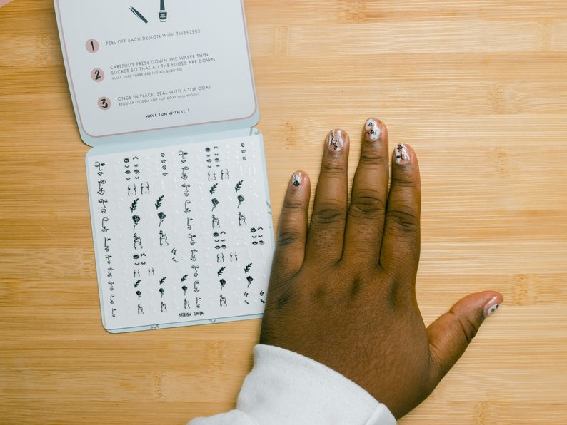 sheet of stickers with some of them shown on a model's hand