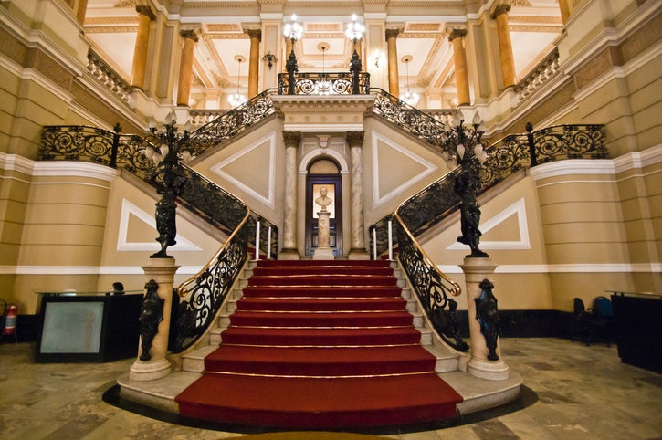 A grande marble staircase with red carpet that leads out on either side