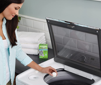 a model dropping a cleaning tablet into a washing machine