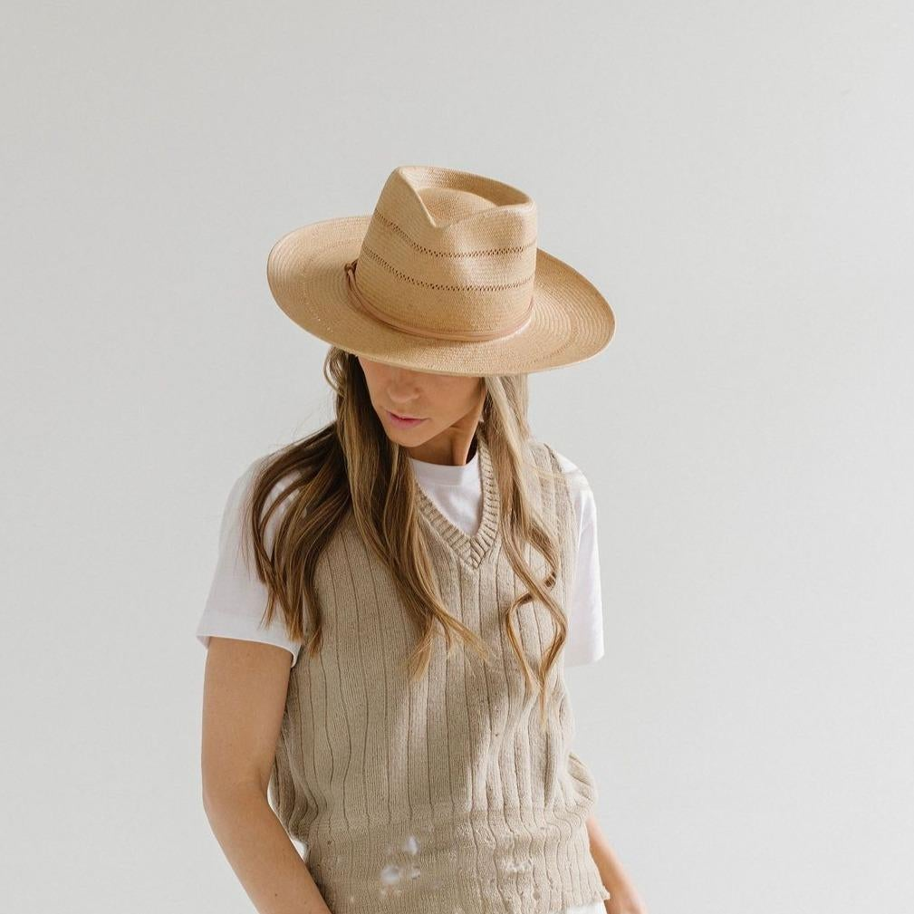 model wearing straw hat with a tie around the top