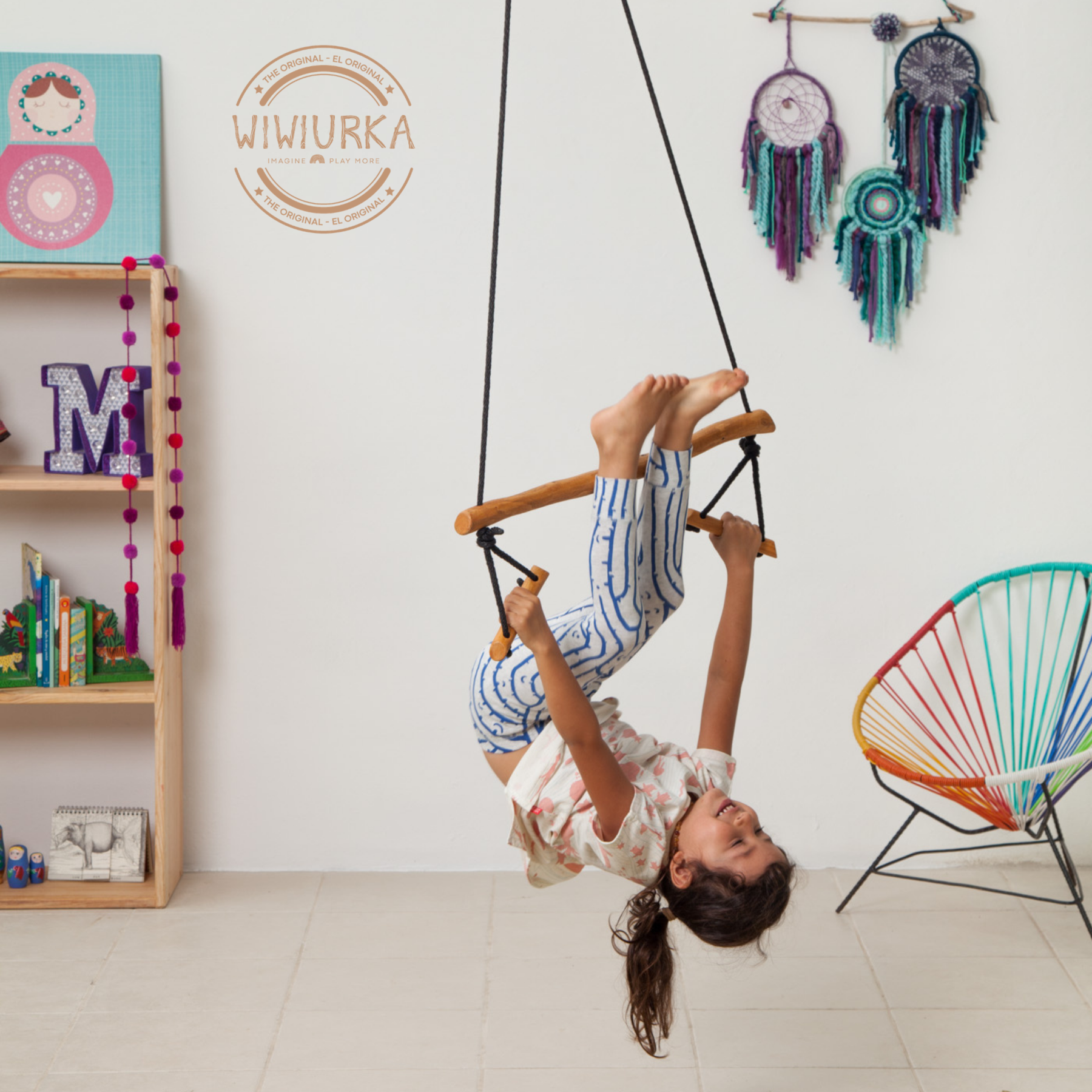 Child swinging upside down from wooden trapeze