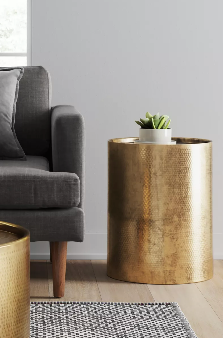 a gold side table next to a couch