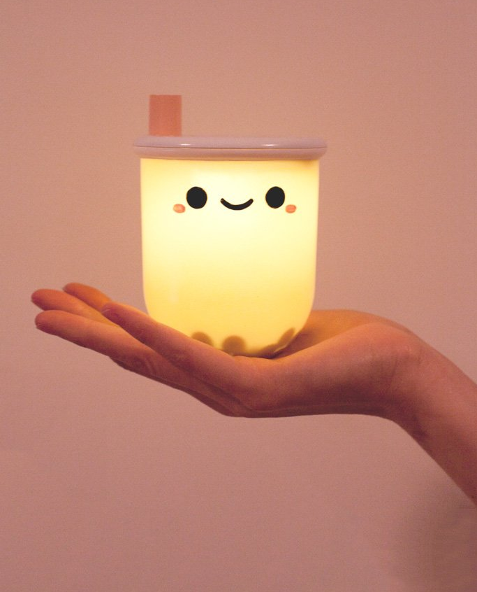 hand holding the light that looks like a boba tea cup with a happy face, with faux boba pearls inside