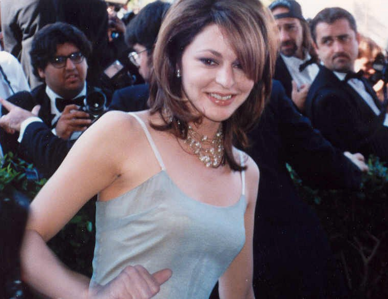 A woman wears a slip dress with several diamond necklaces layered on top of one another. Her hair is down and she has side bangs