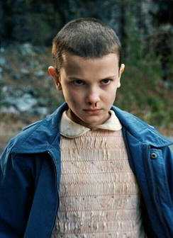Eleven is outdoors looking angry, with blood coming from her nose