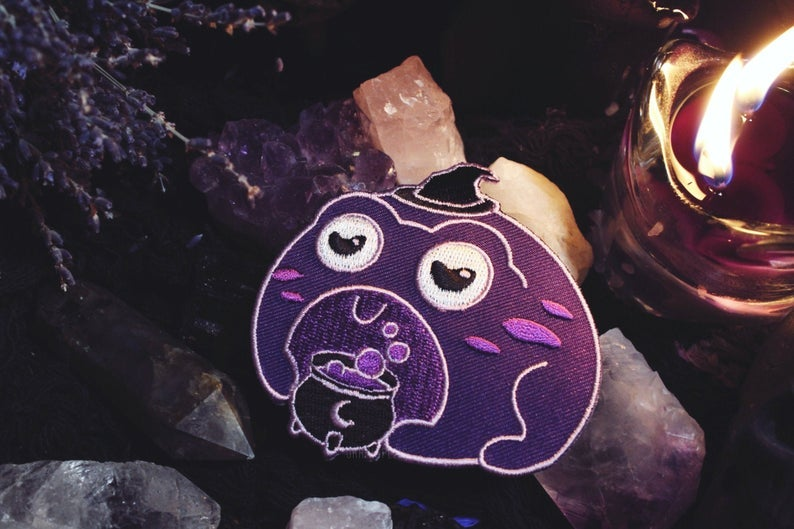 the purple frog wearing a witch hat in front of a cauldron patch