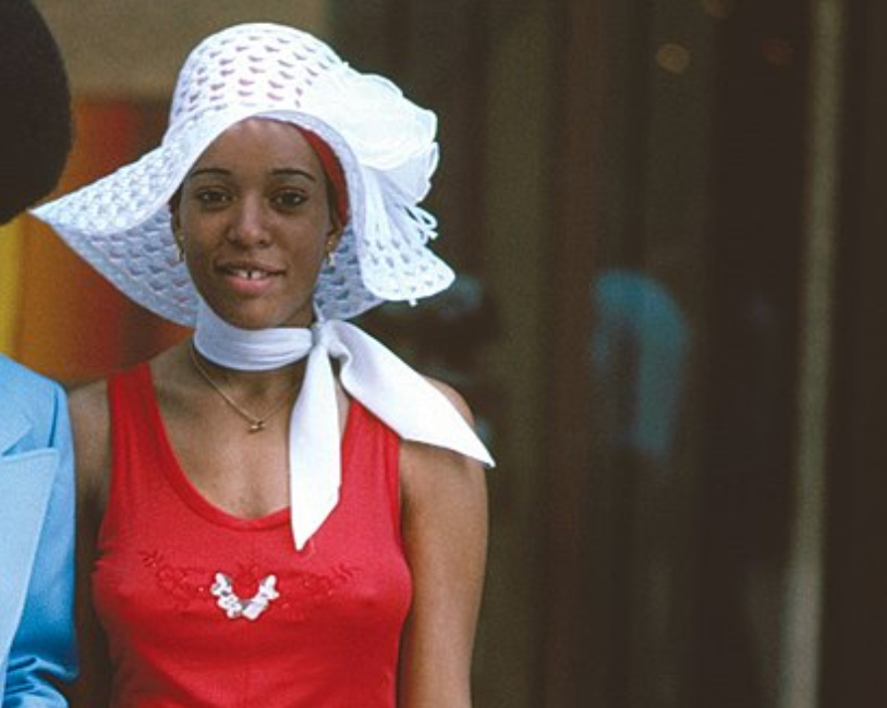 A woman wears a floppy hat and a silk scarf tied around her neck. She wears a small necklace and a cotton dress with no sleeves