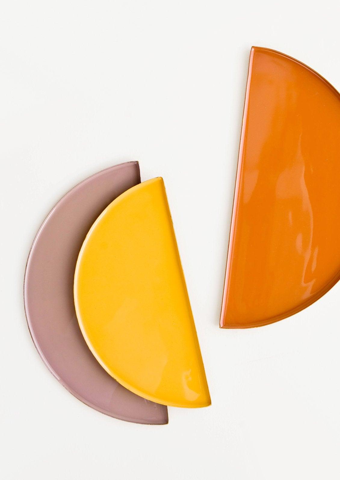 three catchall dishes in yellow, orange, and purple