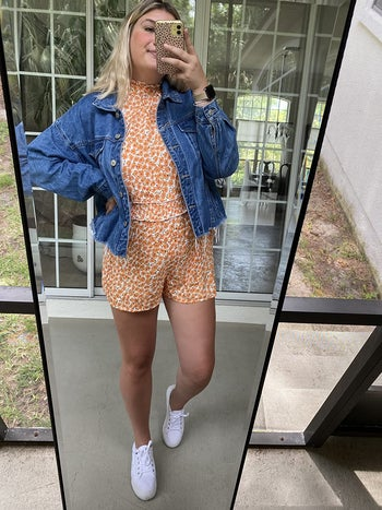 a reviewer wearing the romper in an orange print