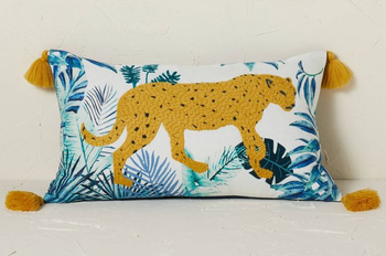 a white pillow with a blue palm print and an embroidered leopard