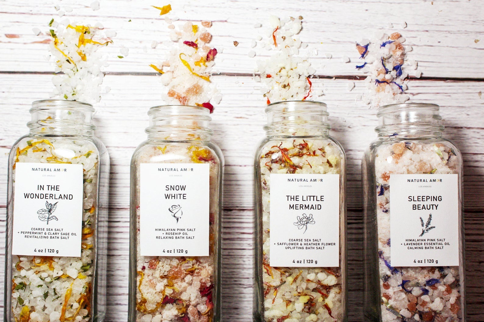 Colorful bath salts in transparent containers themed to fairy tales like Snow White, The Little Mermaid, Alice in Wonderland, and Sleeping Beauty