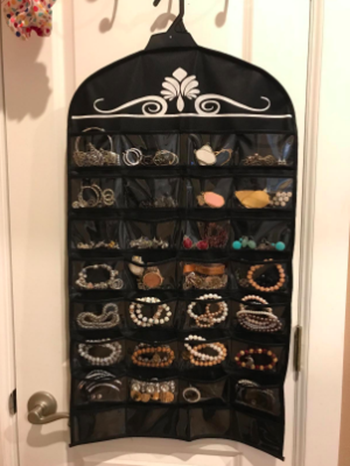 reviewer photo of the organizer on a clothes hanger with lots of clear compartments so you can see the jewelry