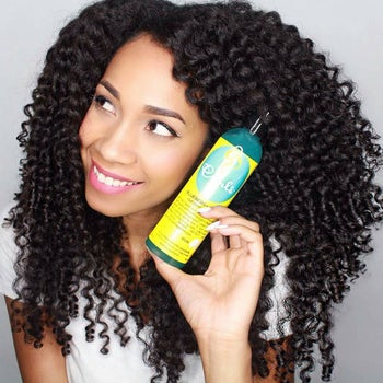 model with curly hair holding the curl control jelly