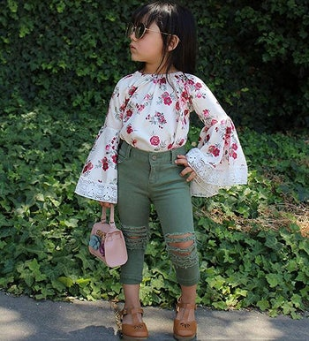 a child in a floral shirt with bell sleeves and ripped green jeans