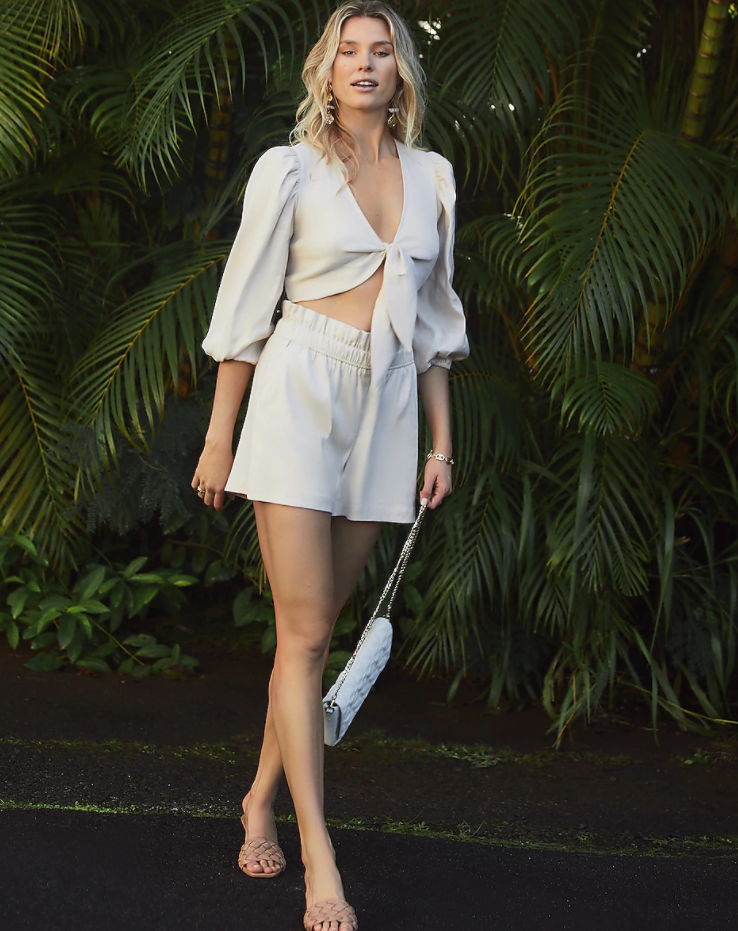 model wearing tie-front crop top with matching shorts in a sand color