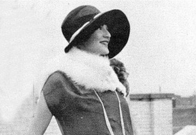 A woman wearing a large hat is looking to the right. She also has a large fur scarf and a short-sleeved polyester shirt