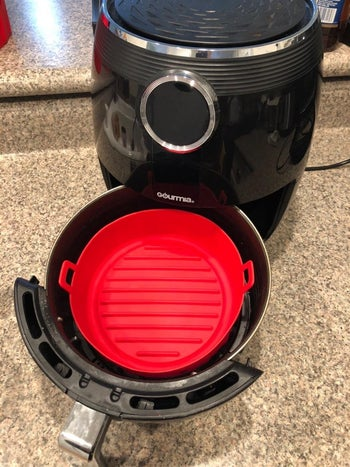 Reviewer's top-down view of the red silicone basket in an air fryer