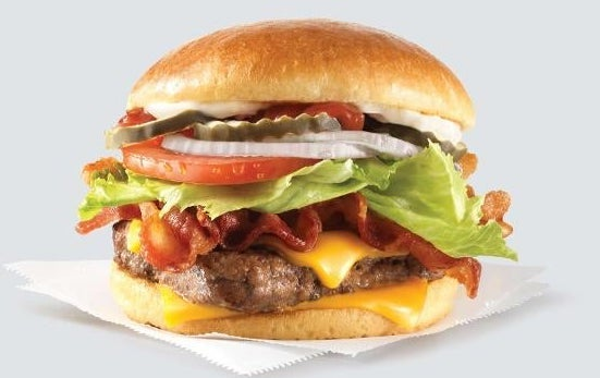 A cheeseburger with bacon, lettuce, tomato, onions, pickles, mayo, and ketchup