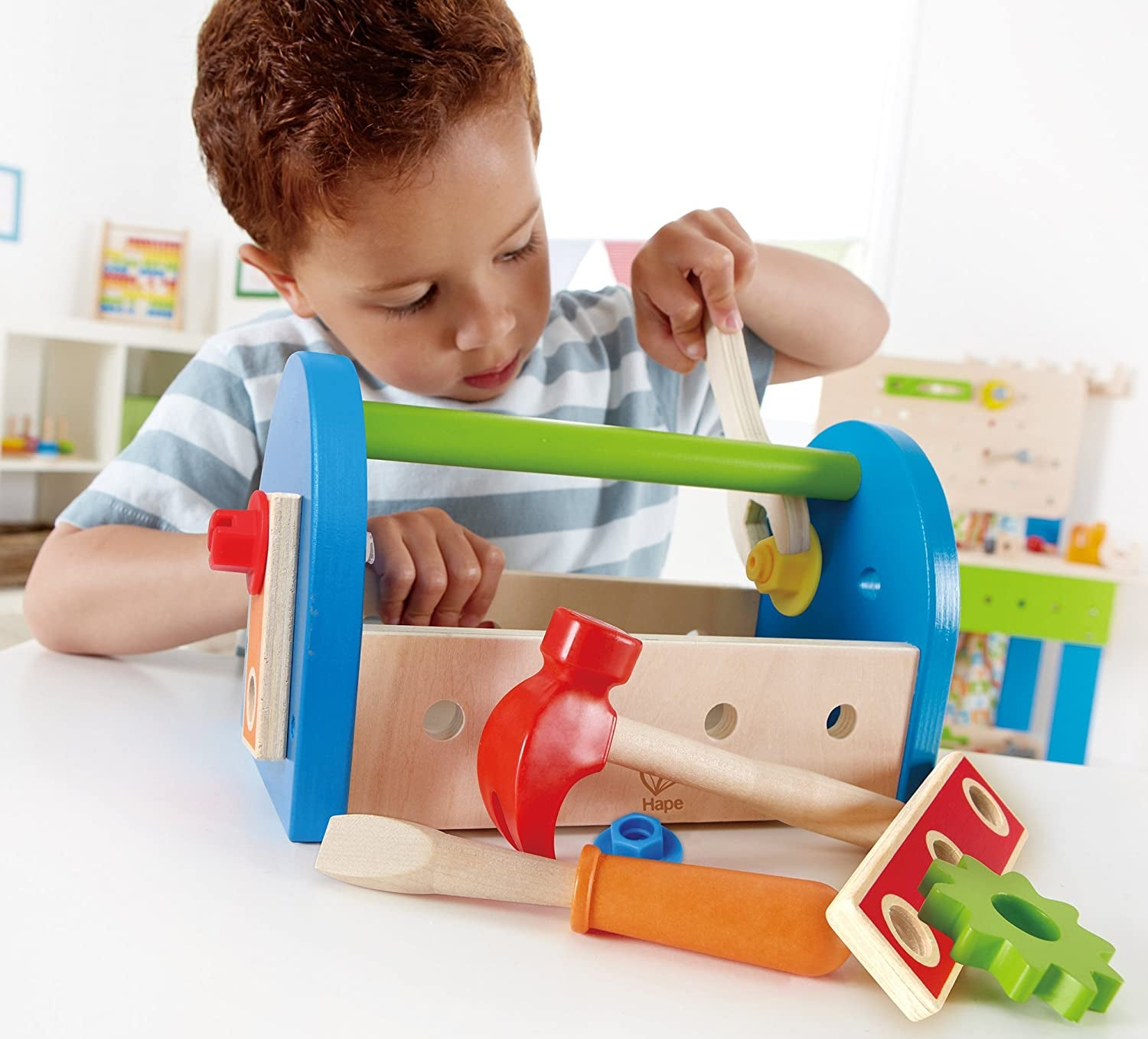 Child model playing with colorful wooden tool kit