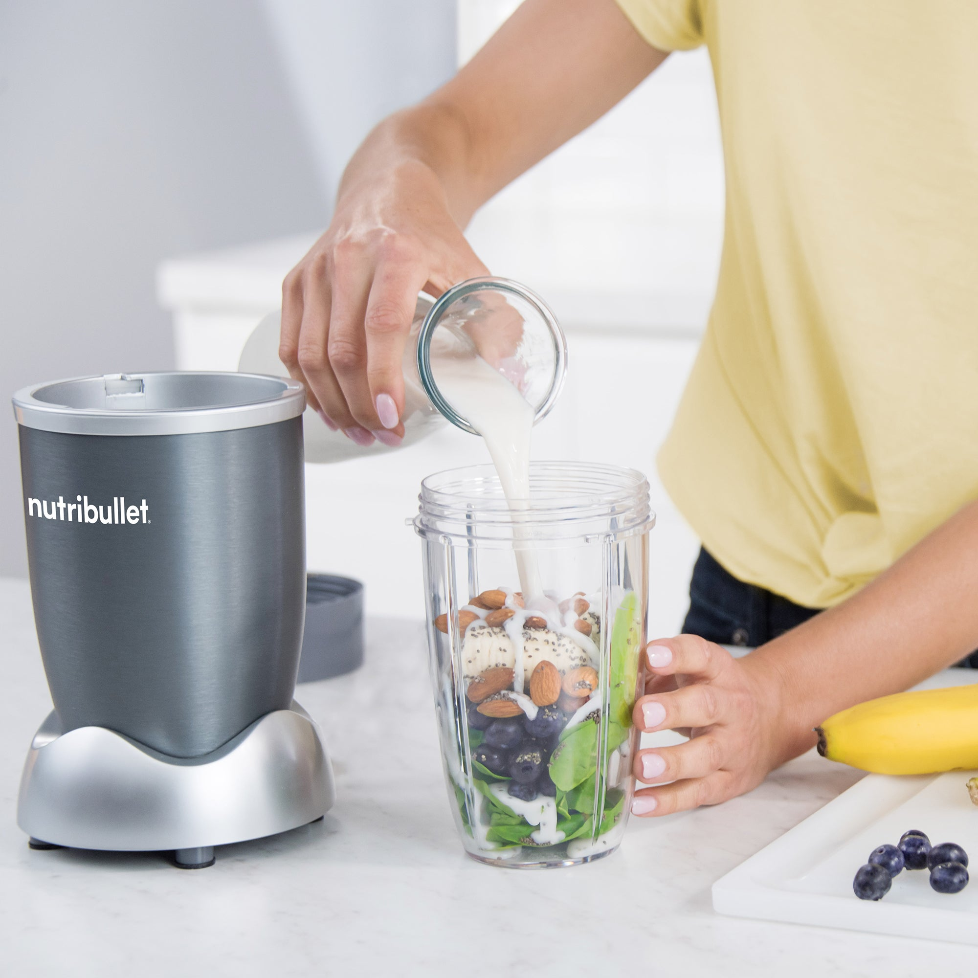 A blender with fruits, vegetables, and nuts in it