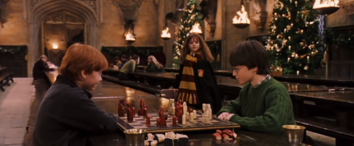 Ron and Harry playing chess in the great hall with Hermione approaching in the background
