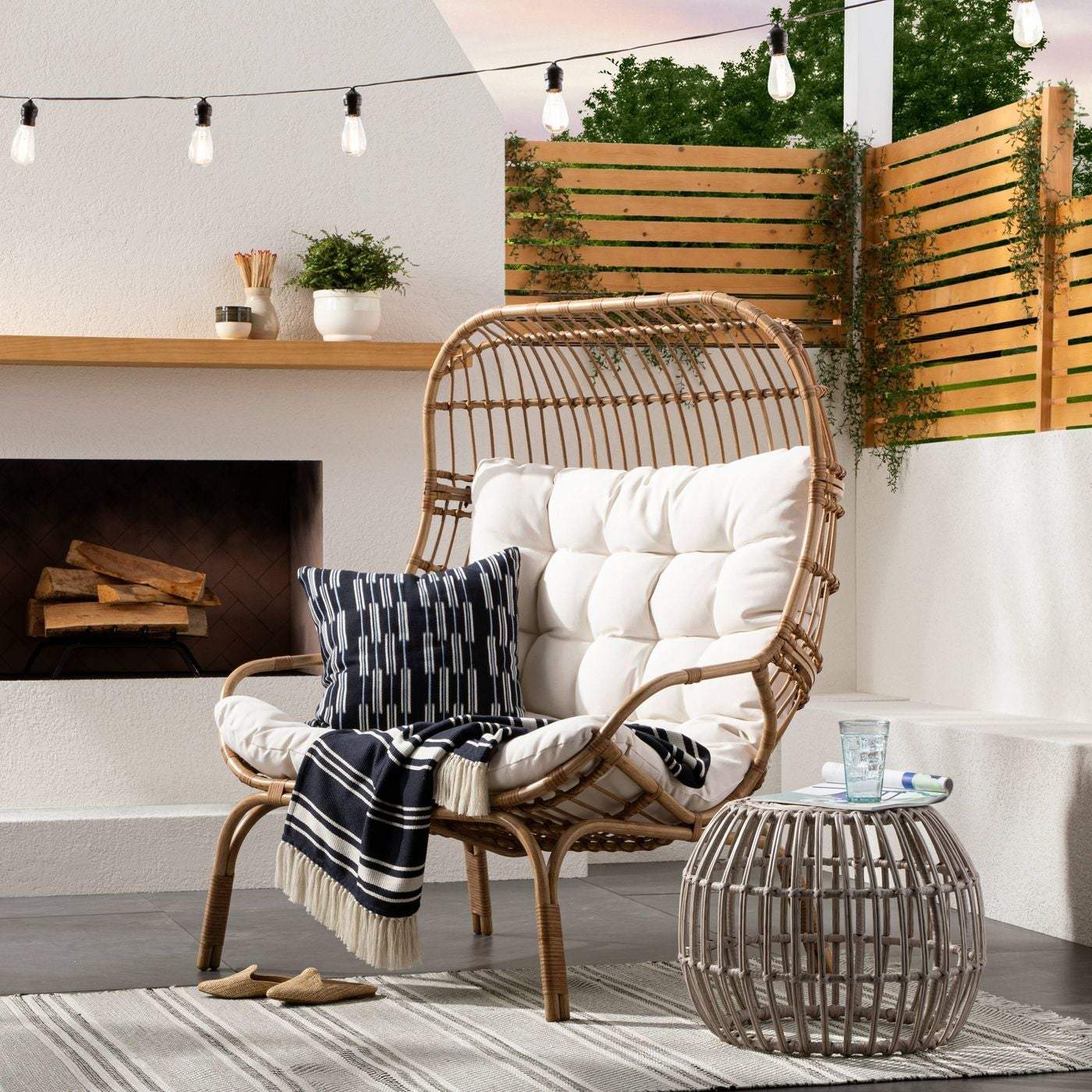 large wicker egg-shaped chair in brown with white tufted cushion in it