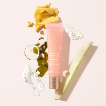 the pink tube of lip balm next to ingredients