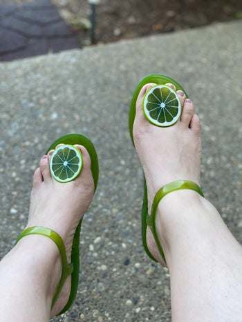 reviewer wearing the flats in green with a lime between the big and second toe
