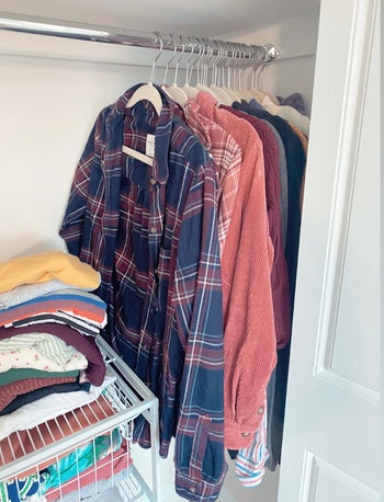 A BuzzFeed' editor's closet with shirts hanging on beige velvet hangers pressed together tightly