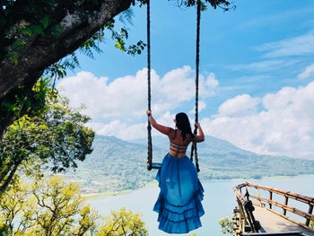 A reviewer in the backless dress on a swing overlooking the water