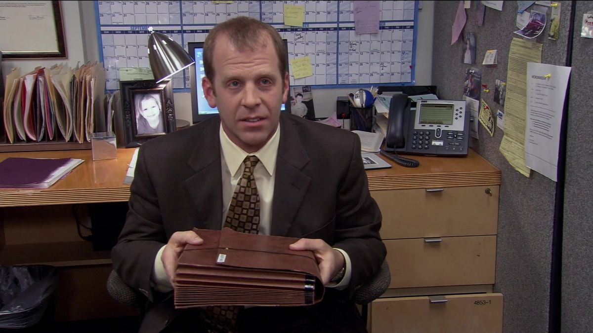 Toby Flenderson is sitting by a desk, holding a brief case
