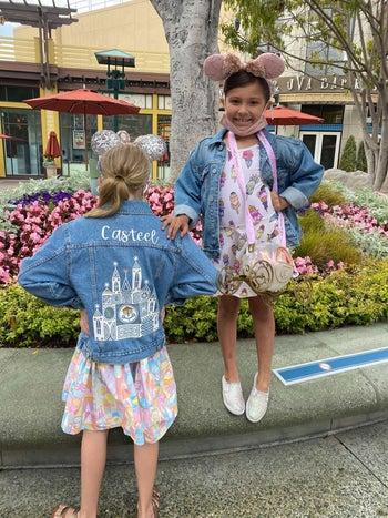 two children wearing denim jackets at Disney
