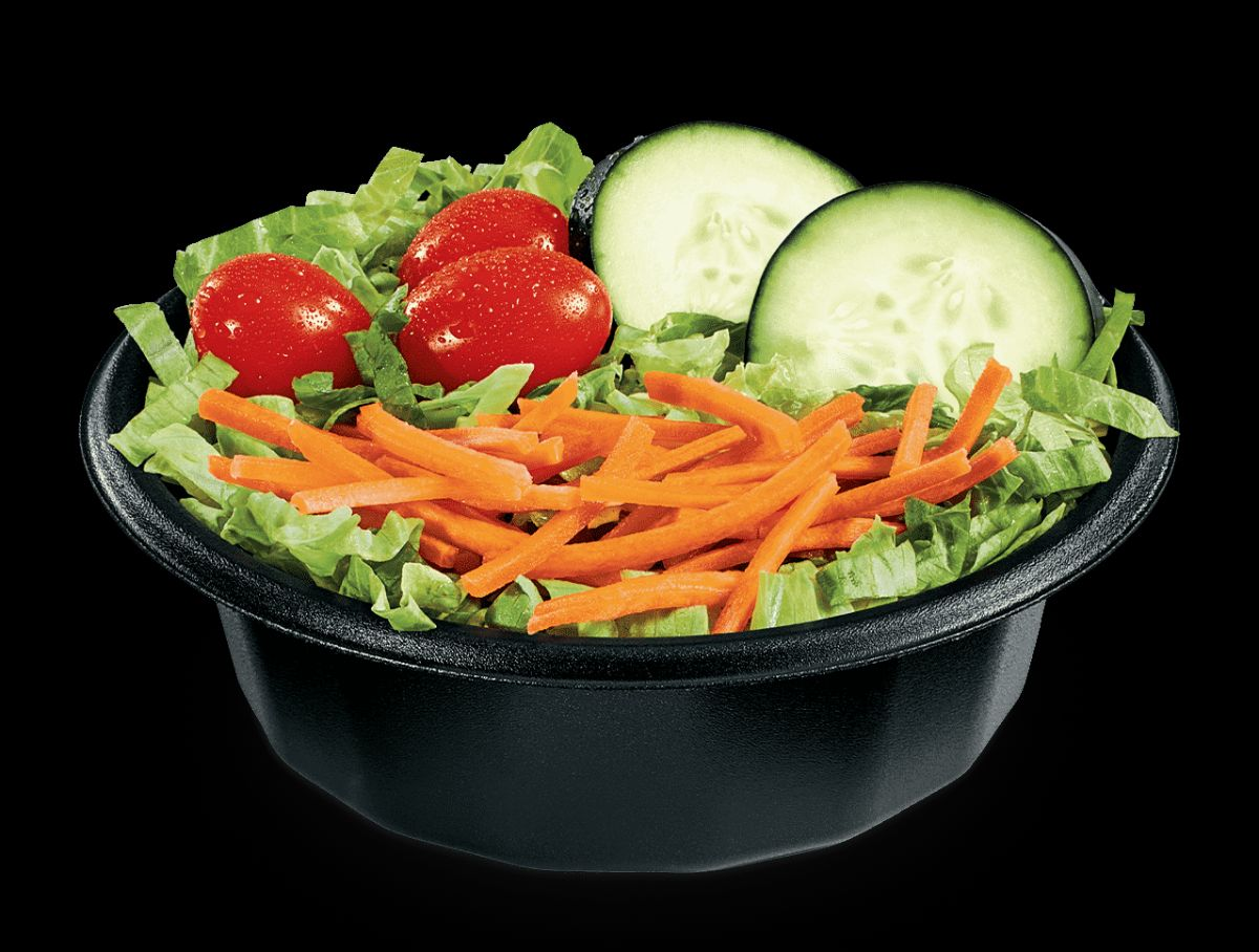 A salad with shredded carrots, tomatoes, and cucumbers