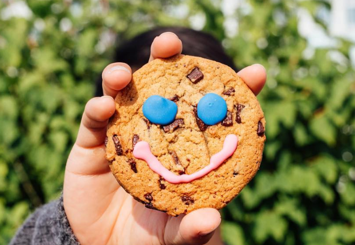 Close up of a cookie with a smile made from frosting on it