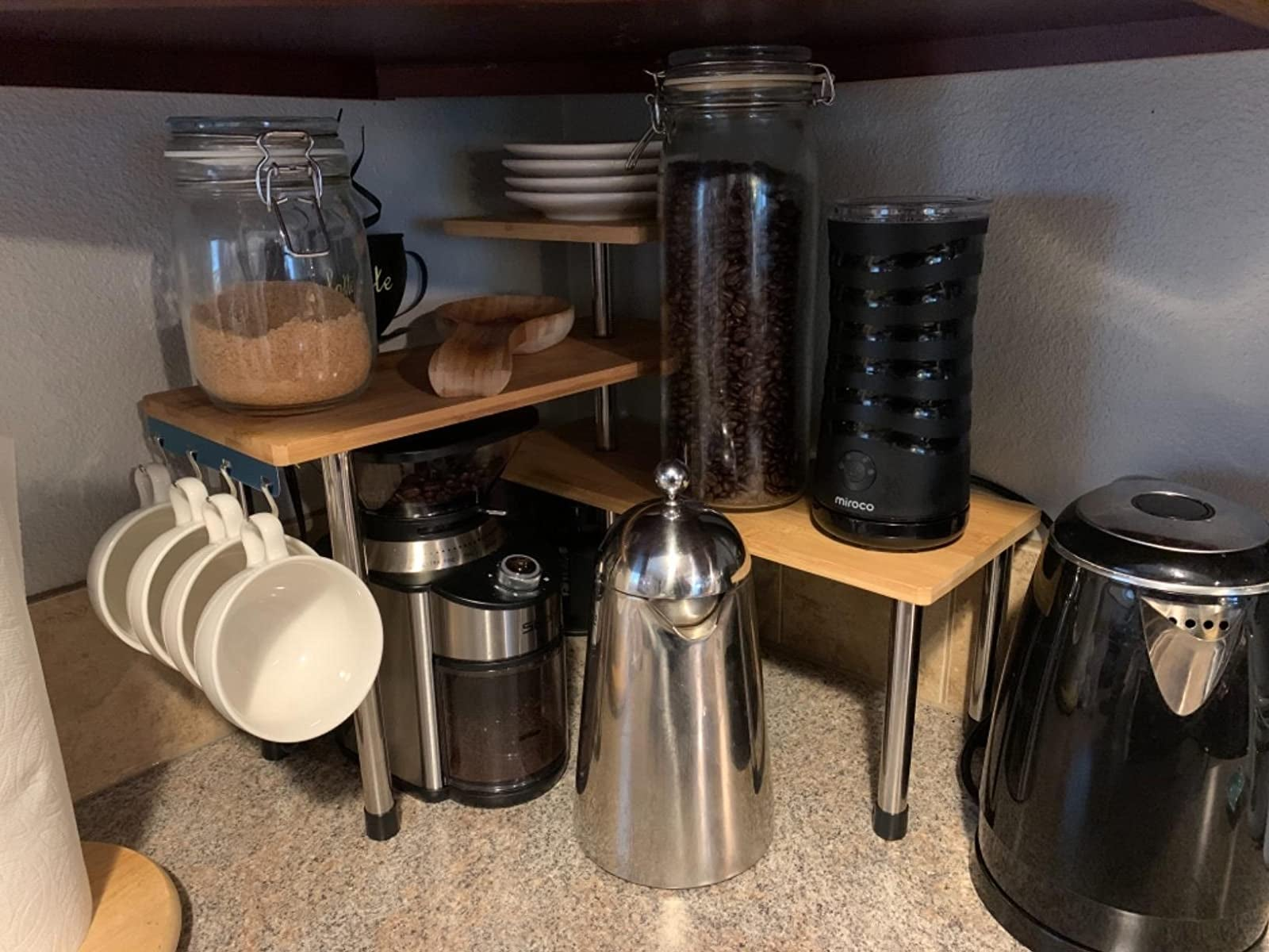 a reviewer's three-tier bamboo shelf holding coffee supplies and mugs