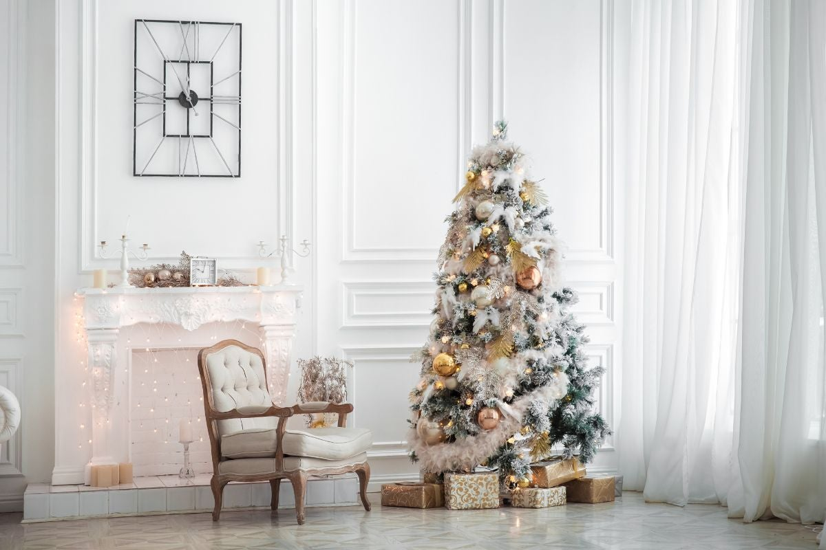 A glamorous Christmas tree in the corner of a living room with snowy garland draped around it and some presents surrounding it