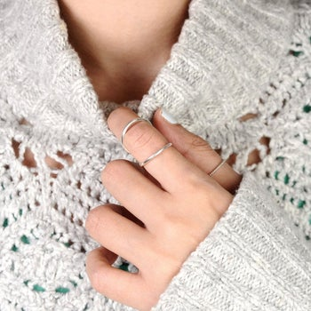 Model wearing silver ring that loops around top and bottom of knuckle